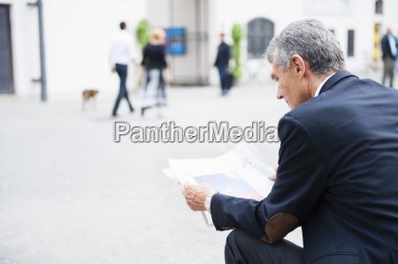 senior businessman sitting in city plaza