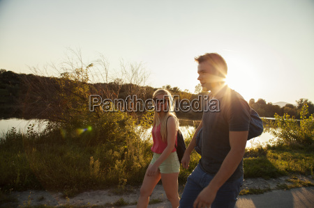 young couple strolling along riverside at