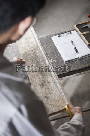 carpenter measuring wood plank with tape