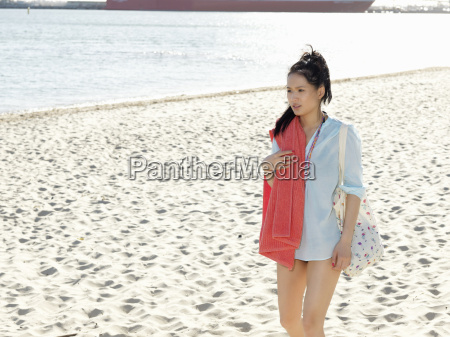 young woman strolling on beach with