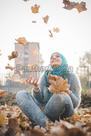 young woman sitting in park throwing