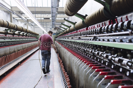 male factory worker monitoring weaving machines
