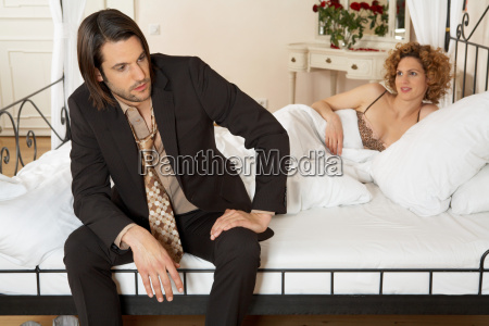 young businessman sitting on bed