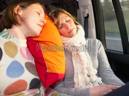 young women sleeping in car