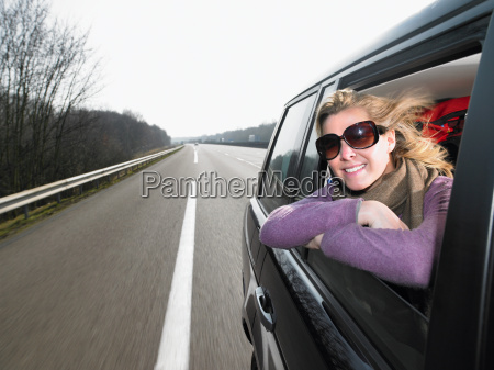 young woman leaning out of car