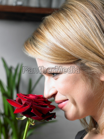 young woman holding red rose up