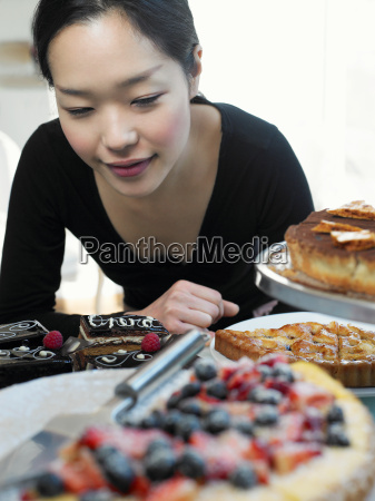 young woman looking at cake display