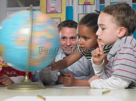 male teacher looking at spinning globe