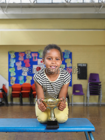 young girl with trophy in school