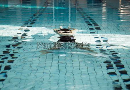 mature man swimming underwater in pool