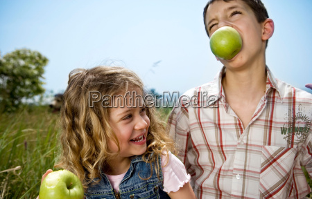 boy holding apple in teeth with