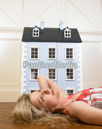 woman next to a doll house
