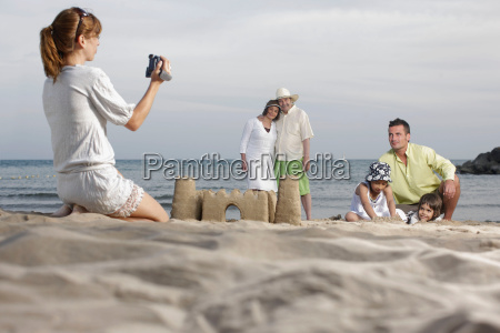 mother taking video of family on