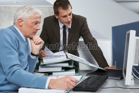 colleagues looking into computer