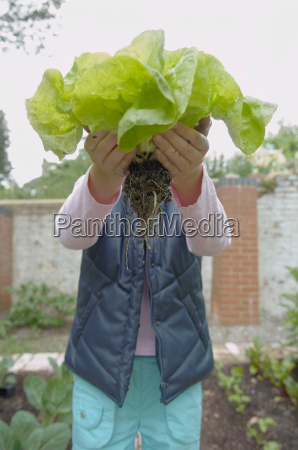 young girl in garden holds up