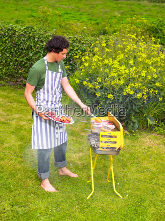 young man placing meat on barbecue