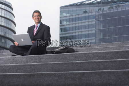 business man with laptop outside