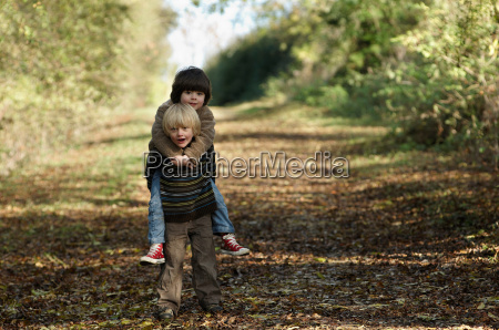 young boy carrying friend in countryside