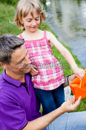 father and daughter with paper boat
