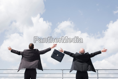two business men throwing arms in