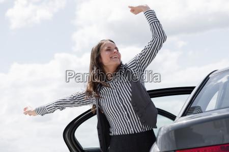 woman stretching near car