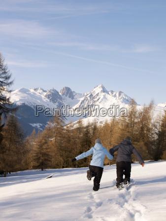 couple running in snow towards mountain