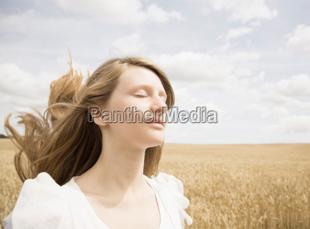 girl with eyes closed in wheat