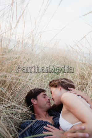 couple lying in reed embracing