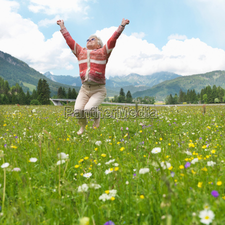senior woman leaping in field of