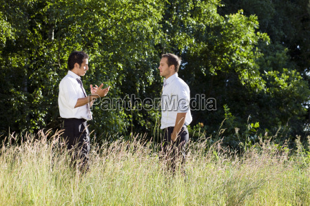 two businessmen talking in nature