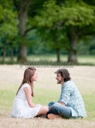 man and woman sitting in field