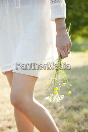 woman holding flowers in countryside