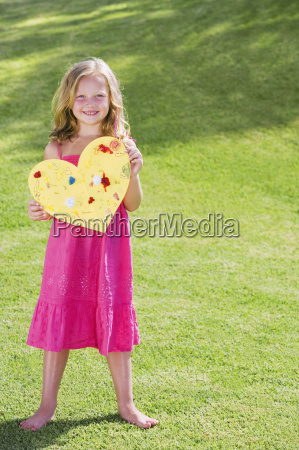 young girl holding paper heart