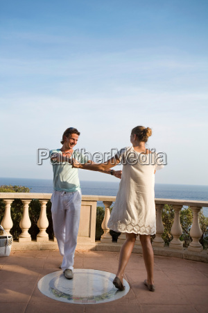 loving couple dance on balcony