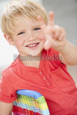young boy holding up three fingers