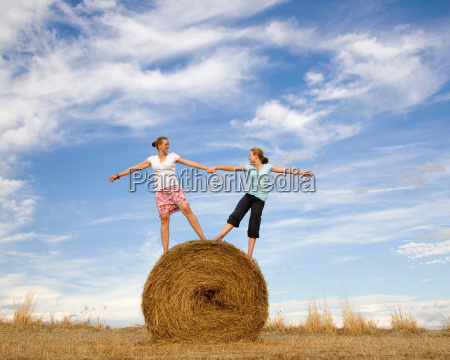 girl and woman standing on hay