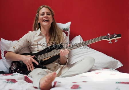 woman playing guitar on bed