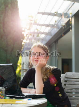 young girl thinking at laptop in