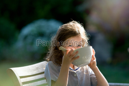 young girl drinking from bowl in