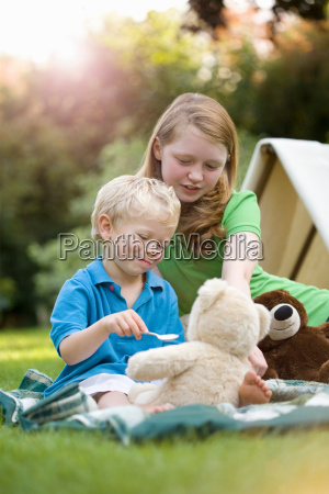 two children feeding a toy bear