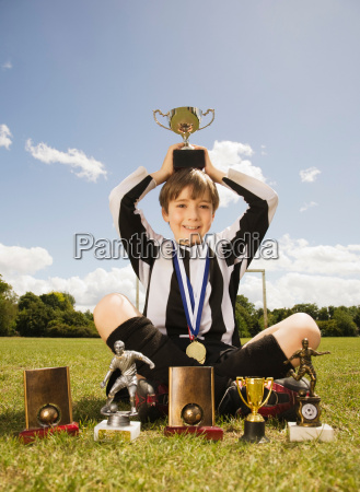 boy footballer with trophies and medals