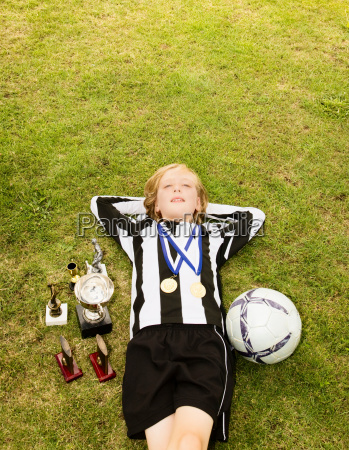 boy on grass with medals and