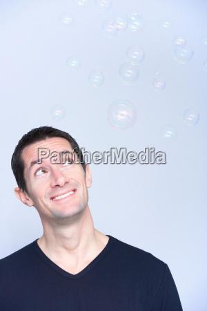 smiling man looking at bubbles