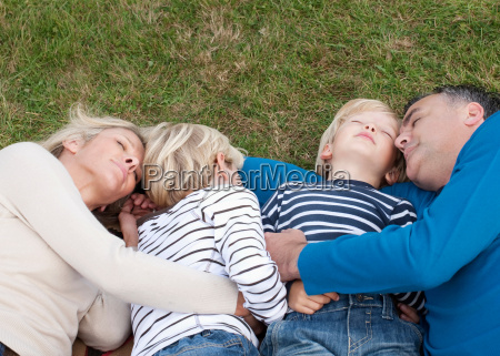 family lying down together on grass