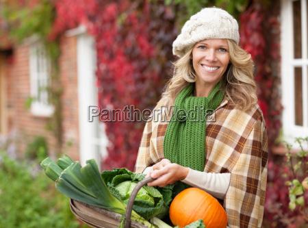 smiling woman with seasonal vegetables
