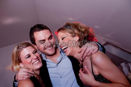 man embracing two women