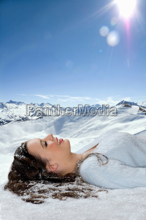 young woman lays in snow