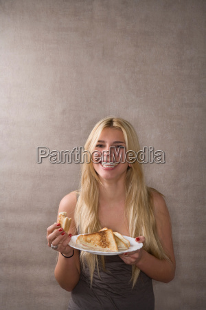 young woman smiles with sandwich