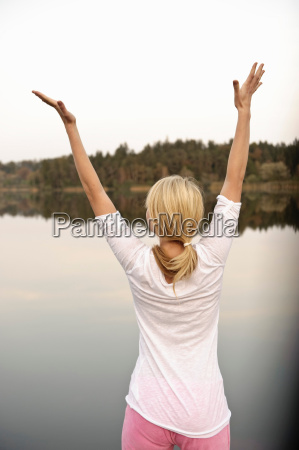 young woman dancing by lake stretching