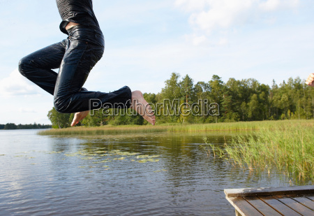 man jumping in the lake with